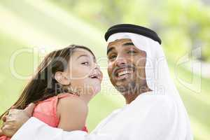 A Middle Eastern man and his daughter sitting in a park