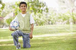 Ein Junge kniet lachend im Gras mit Fussball