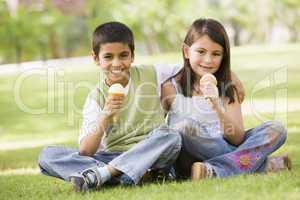 Ein Junge und ein Mädchen lachend auf einer Wiese