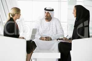 A meeting between a Caucasian businesswoman and a Middle Eastern