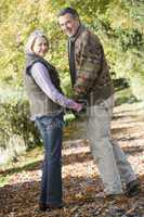 Older couple walking in the forrest in fall time