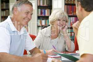 Adult students working together in a library