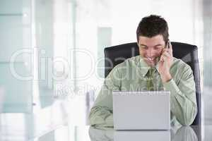 Businessman sitting in office using cellular phone and laptop