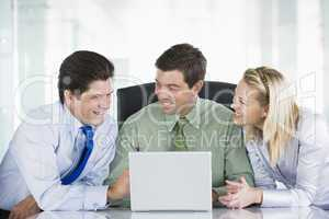 Three businesspeople in a boardroom looking at laptop smiling