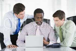 Three businessmen in a boardroom looking at laptop