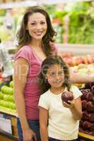 Mother and daughter buying fresh fruit