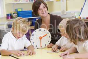 Teacher helping schoolchildren learn to tell time in primary class