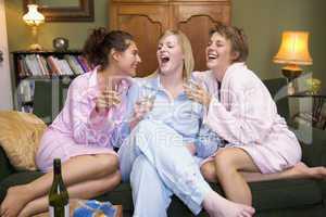 Drei Frauen sitzen im Morgenmantel und Pyjama auf dem Sofa und trinken Sekt