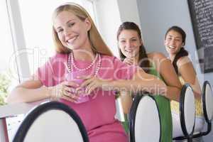 Drei junge Frauen sitzen in einem Cafè