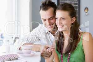 Ein junges Pärchen sitzt Händchen haltend im Cafè