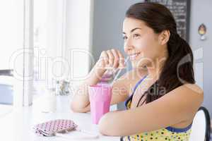 Eine junge dunkelhaarige Frau sitzt im Cafè