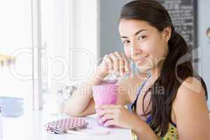 Eine junge dunkelhaarige Frau sitzt im Cafè und nimmt ein Getränk zu sich
