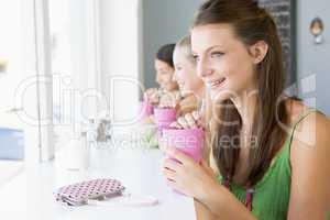 Drei junge Frauen sitzen in einem Cafè und genießen ihre Getränke
