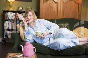A young woman lying on her couch drinking tea