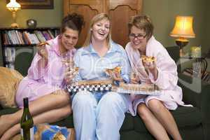 Three young women eating pizza together in their pyjamas