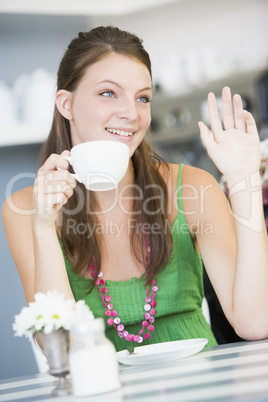 A young woman sitting in a cafe drinking tea and waving