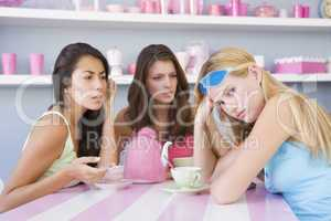 Two young women enjoying a tea party while one sits apart wearin