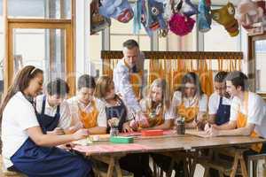 Schoolchildren and teacher sitting around a table in art class