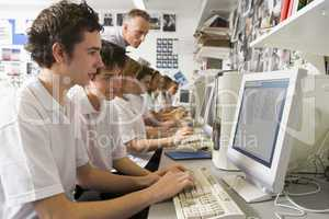 Row of schoolchildren studying in front of a computer