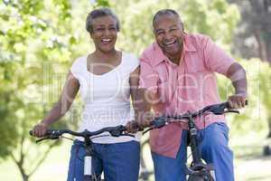 Ein älteres dunkelhäutiges Pärchen fährt Fahrrad