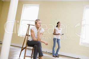 Two women with ladder in empty space holding paper