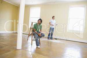 Two men with ladder in empty space holding paper and thinking