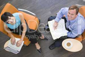 Two businesspeople sitting indoors with coffee laptop and folder