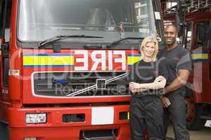 Eine Feuerwehrfrau und ein Feuerwehrmann vor einem Löschfahrzeug