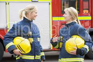 Zwei Feuerwehrfrauen stehen vor einem Löschfahrzeug und schauen sich an