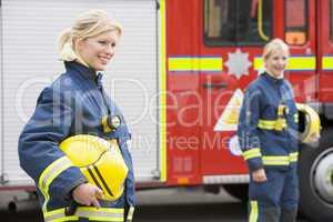 Zwei Feuerwehrfrauen sttehen vor einem Löschfahrzeug