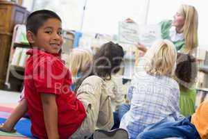 Kindergarten teacher reading to children in library, boy looking