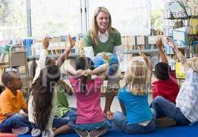 Kindergarten teacher and children with hands raised in library