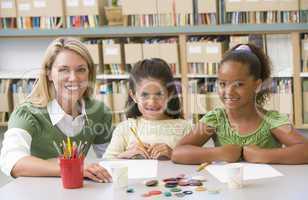 Kindergarten teacher sitting with students in art class