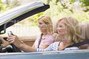 Two women in convertible car smiling