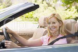 Woman in convertible car smiling