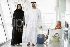 Couple walking through airport departure lounge