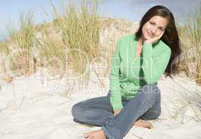 Young woman relaxing amongst dunes