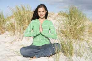 Young woman meditating amongst sand dunes