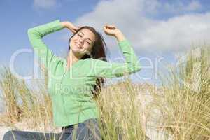 Young woman stretching in dunes