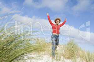 Young woman stretching amongst dunes