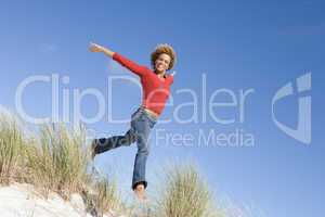 Young woman jumping amongst sand dunes