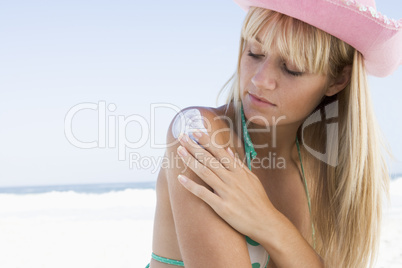 Young woman applying sun protection product