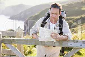 Man relaxing on cliffside path holding map