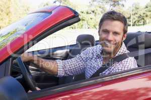 Man in convertible car smiling
