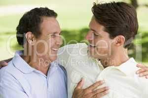 Two men standing outdoors bonding and smiling