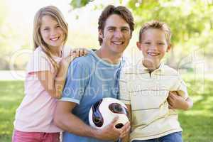 Man and two young children outdoors holding volleyball and smili