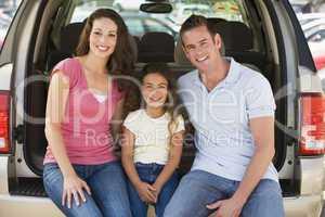 Family sitting in back of van smiling