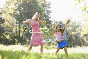 Woman and young girl outdoors using hula hoops and smiling