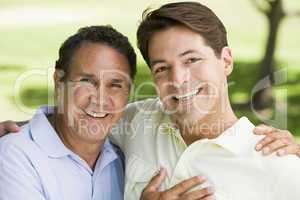 Two men outdoors embracing and smiling