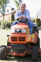 Man outdoors on lawnmower smiling